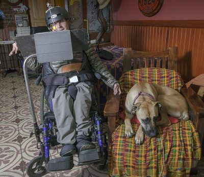 Julius with his dog, Jesse. Here he can be seen in his wheel chair and working on his iPad.