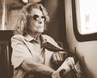 An elderly lady wearing dark glasses is seated on public transportation.