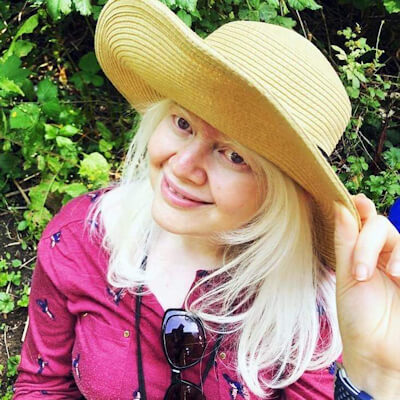 A blonde lady wearing a pink top and sunhat with dark glasses strung around her neck smiles at the camera.