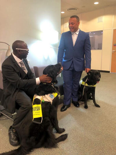 The article author with a black guide-dog greets a fellow blind man and his seeing eye dog.