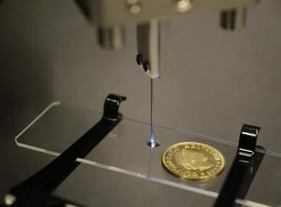 Researchers used an optical fiber housed inside the needle pictured to deliver light for 3-D printing microstructures. The light selectively hardens volumes inside the droplet of photopolymer on the glass slide. The new system could one day allow 3-D printing inside the body - Image Credit: Damien Loterie and Paul Delrot, École Polytechnique Fédérale de Lausanne.