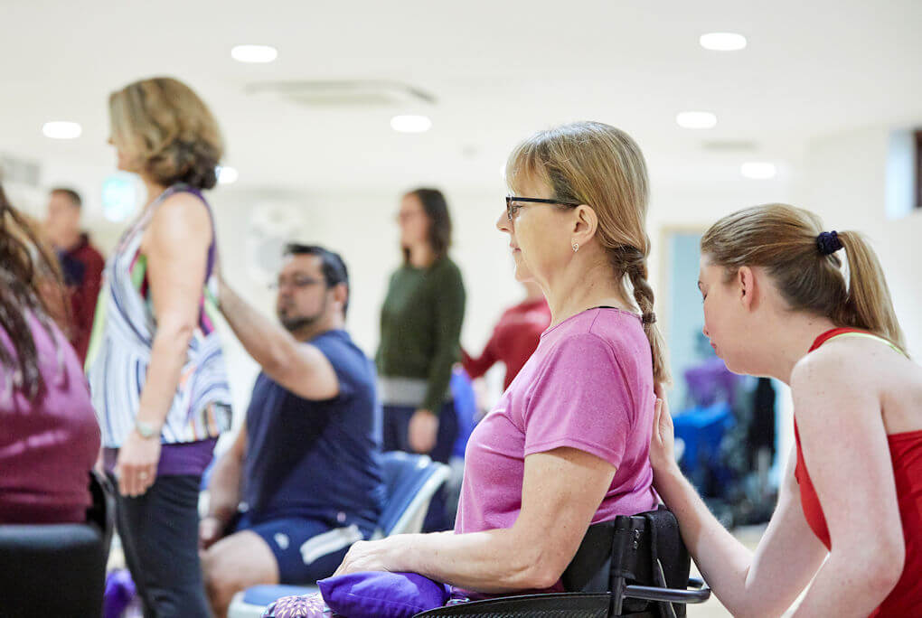 Seated woman receives assistance from instructor during Adaptive Yoga group session.