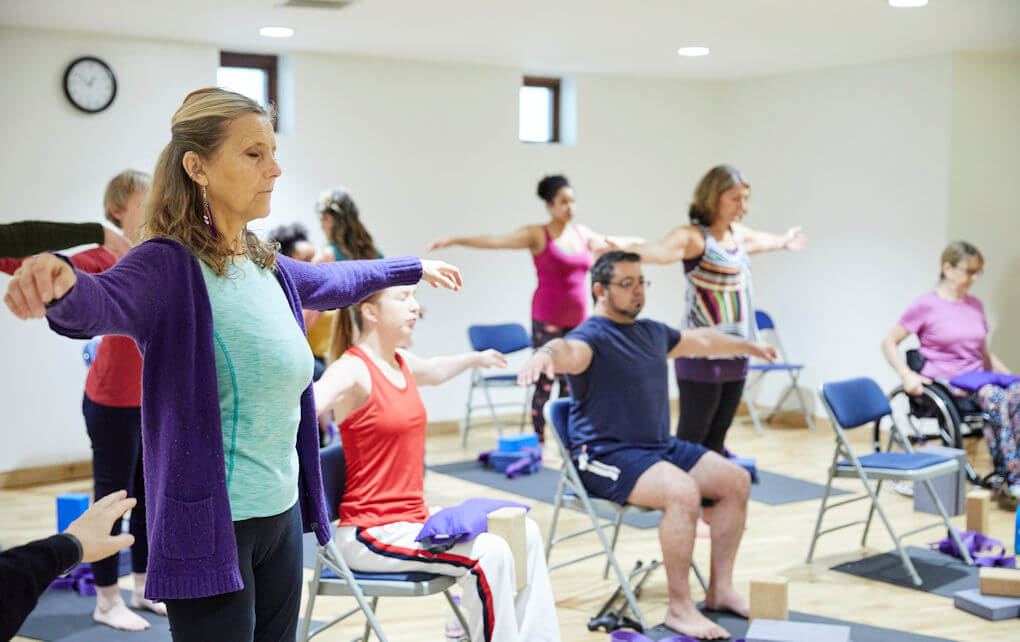 Photo shows a number of both standing and seated people during an Adaptive Yoga group class session.