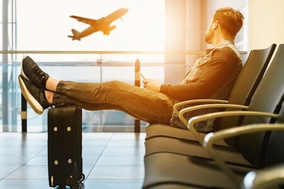 A man sits in an airport lounge resting his legs on a suitcase while watching a plane takeoff.