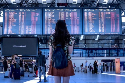 A woman wearing a skirt with her back to the camera studies the arrivals and departures board at an airport.