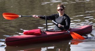 Woman trying out the Angle Oar system in purple kayak