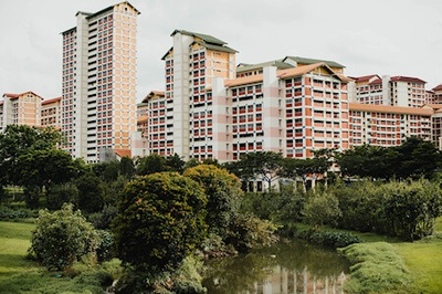 White and brown apartment buildings with narrow tree lined river in foreground - Photo by chuttersnap on Unsplash.