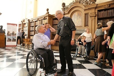 Archbishop of Canterbury, Justin Welby, shakes hands with a man in a wheelchair at Lambeth Palace. Other people can be seen in the background - Photo Credit: Lambeth Palace.