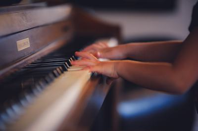 A blurred shot of a child playing the piano - Photo Credit: Clark Young on Unsplash