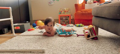 Baby playing with toys on carpeted floor.