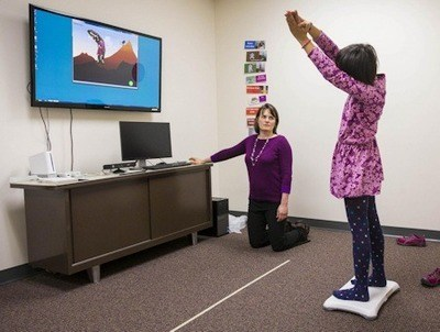 Brittany Travers, an investigator at the University of Wisconsin-Madison Waisman Center and an assistant professor of kinesiology, works with a study participant while she plays a video game designed to help youth with autism improve their balance. It may also help improve some of their autism-related symptoms - (Andy Manis).