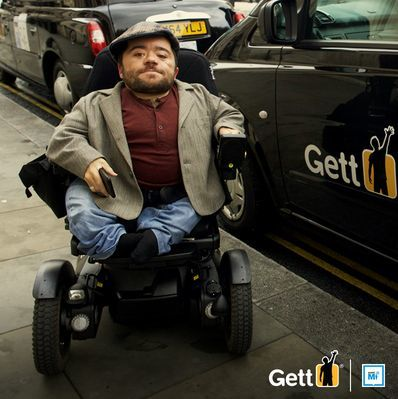 Disabled man in wheelchair alongside a Black Cab