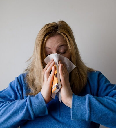 Woman in blue sweater blowing her nose into a tissue. A small orange pack of tissues is also in her hands.