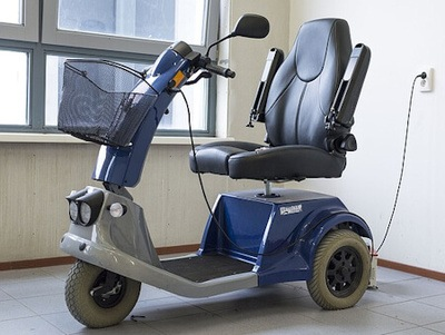 A blue mobility scooter is pictured having the battery re-charged indoors.
