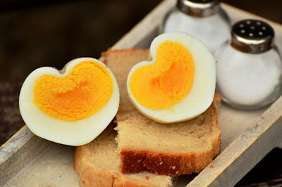 Boiled egg sliced in 2 heart shaped halves on top of bread beside salt and pepper shakers on a wooden tray.