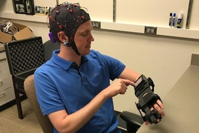 Medical resident Jarod Roland, MD, tries out a device that detects electrical activity in his brain and causes his hand to open and close in response to brain signals. A new study shows that this device can help chronic stroke patients recover some control over their paralyzed limbs. Photo Credit: Leuthardt lab.
