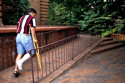 In this particular view, a brick switch-back ramp with black metal railings, has been added to the entrance on an older, traditionally-designed building. The ramp begins not far from where the stairs are positioned, making the accessibility route short, and easy to find. The result makes the access route easier for visitors, demonstrating that some ramps, as well as other stepless-entrance features, can benefit people who are ambulatory, as well as those who use wheelchairs - Creator: CDC/ Richard Duncan, MRP, Sr. Proj. Mngr, North Carolina State University, The Center for Universal Design.