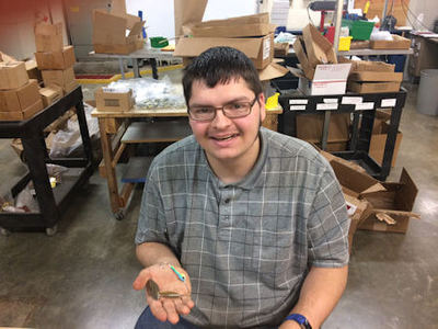 JSI employee Chris Ingram holds a fishing lure, one of many he assembles for JSI customer Omega Custom Tackle Company.
