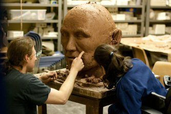 Sculptor Carl Goines shows Volunteer Amanda Stahl how to create the details that bring the sculpture to life