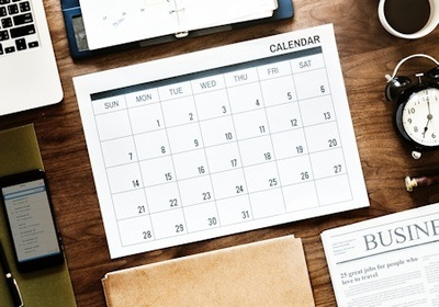 A desktop calendar of events sits on a cluttered desk - Photo by rawpixel on Unsplash.