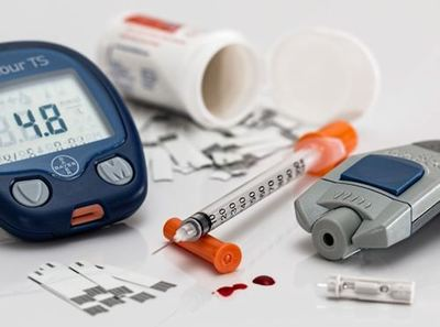 Image shows small diabetes blood sugar meter - reading 4.8 - a finger pricker, syringe, and blood glucose test strips.