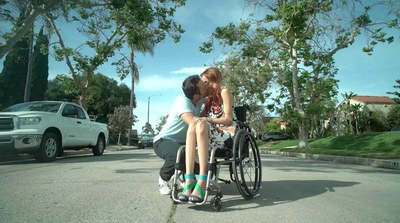 In the middle of a quiet street a man is kissing a red headed girl who is using a wheelchair.