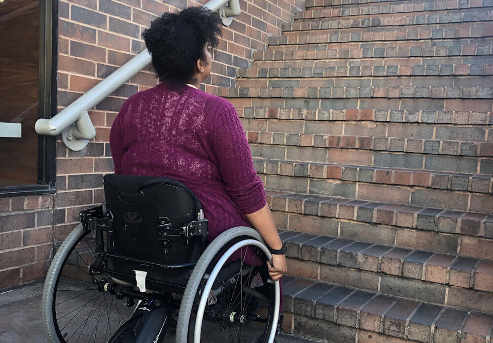 A young African American woman in a wheelchair looking up a flight of stairs.