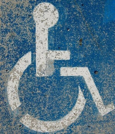 Old and scuffed painted stencil of the disability symbol - Photo Credit: Matt Artz on Unsplash.