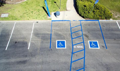Ableism is an understudied topic, but one that requires attention to increase inclusion and support for the disabled community. Image shows 2 disabled parking spaces outlined in blue with no parking written between them.