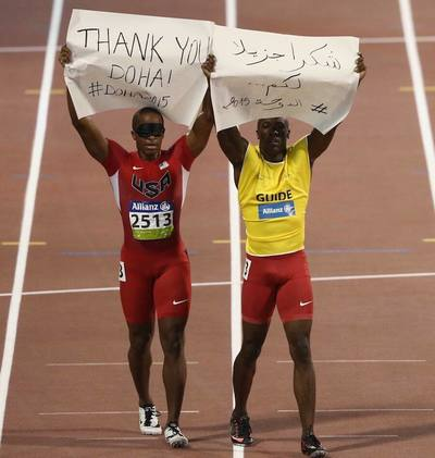 David Brown of USA holds up a banner after the Men's 100m T11 final