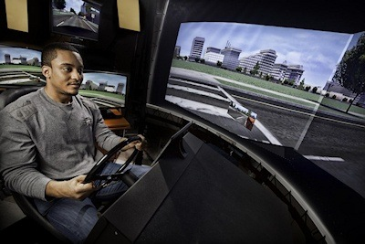 A research assistant at the University of Virginia School of Medicine demonstrates UVA high-tech driving simulator. (He is not a participant in the driving study) Image Credit: Jackson Smith - UVA Health System.
