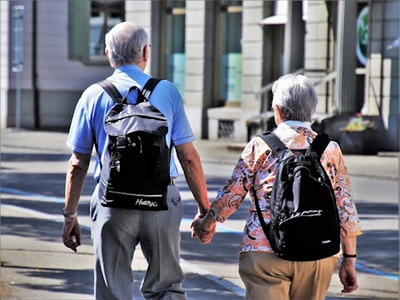 An elderly couple wearing backpacks and with their backs to the camera stroll hand in hand leisurely through a city area.