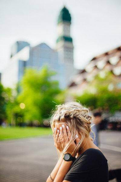 Embarrassed woman hiding face in embarrassment. Blurred images of buildings can be seen in the background.