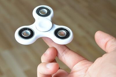 White fidget spinner balancing on a childs finger.
