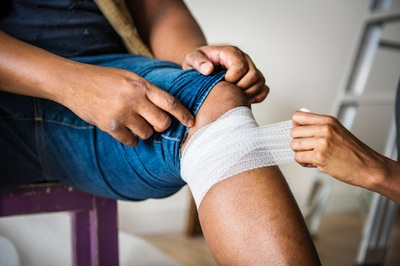 Person getting a bandage applied below the knee by another person - Photo by rawpixel on Unsplash.