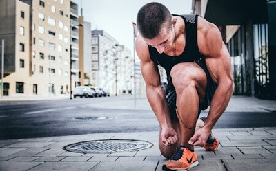 A muscular man tying his running shoe while he kneels on a sidewalk. Staying fit can prevent many future health problems.