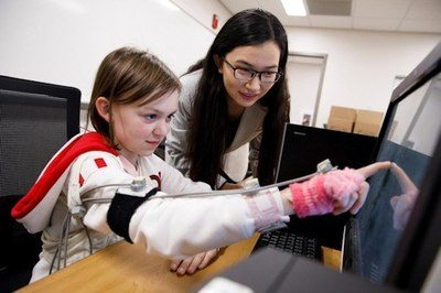 IU Ph.D. student Di Wu directs a volunteer as she touches images on a screen using a device designed to track miniscule fluctuation in the arm's movement. IU-led research suggest physical movement is an accurate method to diagnose neurodevelopmental disorders, including autism - Image Credit: James Brosher, Indiana University.