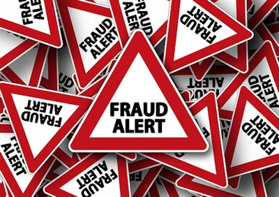 White with red border triangular road signs with the words - Fraud Alert - in black letters.