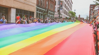Portland, Maine residents carry the large rainbow flag down Congress Street during the annual Pride parade - Photo by Mercedes Mehling on Unsplash.