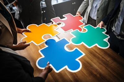 Three people holding large colored puzzle pieces and assembling them on a brown wooden table - Photo by rawpixel on Unsplash.