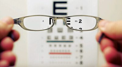 Person holding eyeglasses up in front of Snellen eye chart - Photo by David Travis on Unsplash.