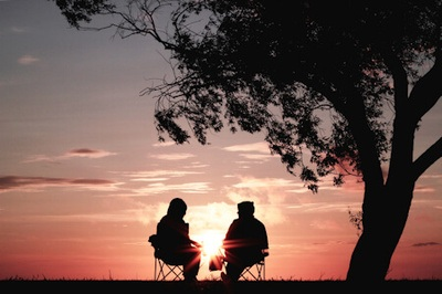 The golden years - silhouette of two people sitting in chairs under a tree watching a pink sunset.
