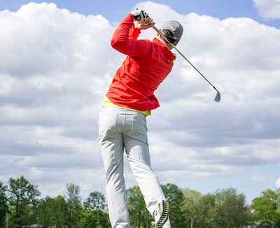 Man in red long-sleeved top and white pants playing golf - Photo by Court Prather on Unsplash.
