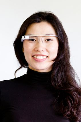 Smiling woman wearing Google Glass
