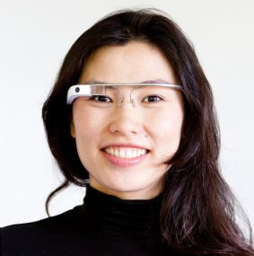 Head and shoulders photo of a smiling woman wearing Google Glass - (Image not part of press release).