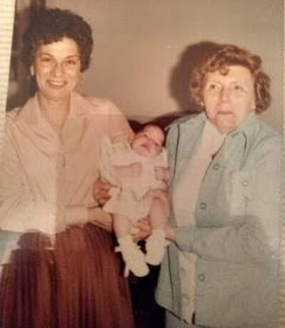 Our daughter being held by her grandmothers.