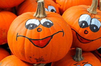 Orange Halloween pumpkins with faces painted on them.