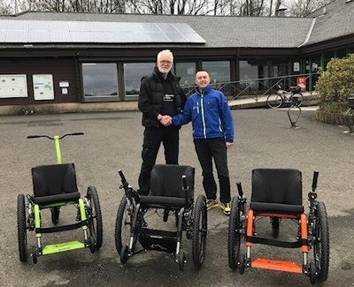 Roger Crawford hands over Mountain Trike demo models to David Hill.