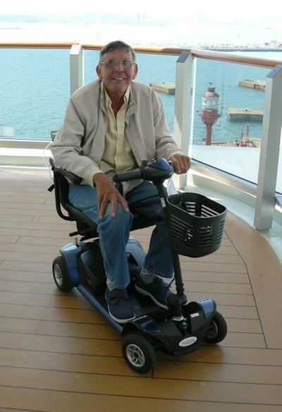 Happy man in mobility scooter on cruise ship deck