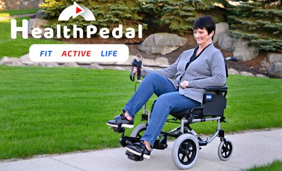 Woman pedaling the HealthPedal Wheelchair along a path in a park. The HealthPedal logo is at the top left of the image - Image Credit: PedalWheelchair.com